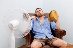 Мужчина пытается справиться с жарой при помощи вентилятора